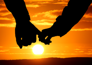 Two holding hands in front of setting sun