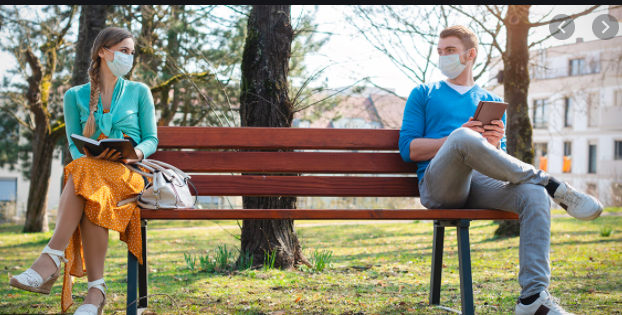 Two people on opposite ends of park bench wearing masks